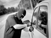 Thief breaks into a car door — Stock Photo