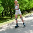 Girl roller-skating in the park - Stock Photo