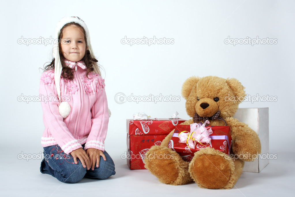 可爱的小女孩坐在附近的礼品和玩具熊– 图库图片
