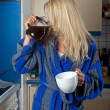 Sleepy blonde woman drinking coffee from the pot — Stock Photo