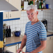 Handsome man cooking pasta in the kitchen - Stock Photo