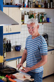 Handsome man cooking pasta in the kitchen — Stock Photo