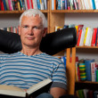 Handsome man reading in a chair — Stockfoto