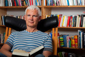 Handsome man reading in a chair — Stock Photo