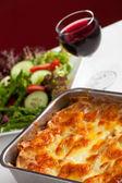 Baking dish with lasagna and salad — Stock Photo