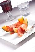 Ham en meloen segmenten op een plaat — Stockfoto
