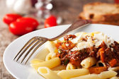 Penne bolognese and parmigiano cheese — Stock Photo