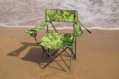 зеленый стул в песке на берегу моря. — Стоковое фото