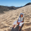 Stock Photo: Boy sitting on sand dune in Egypt