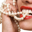 Woman smiles showing white teeth and pearly necklace — Stock Photo #5688688