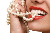 Woman smiles showing white teeth and pearly necklace — Stock Photo