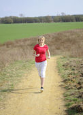 Woman jogging on a dirt road — Stock Photo