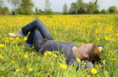 Woman lies on a flower meadow — Stock Photo