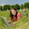 Woman with laptop on a meadow — Stock Photo