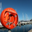 Large orange lifebuoy in Weymouth harbour with yachts behind - Stock Photo