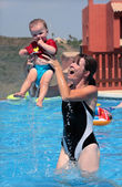 Young woman and daughter playing in the swimming pool — Stock Photo