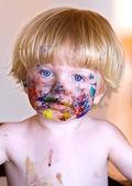 Joven con la cara cubierta de pintura colorida — Foto de Stock