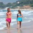 Two young beautiful tanned women walking along sandy beach — Stock Photo