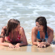 Two attractive young women lying on a sunny beach near the water — Stock Photo