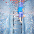Underwater photo of young boy climbing out of swimming pool — Stock Photo