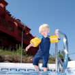 Stock Photo: Young boy with arm bands climbing into swimming pool