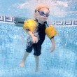 Stock Photo: Young boy jumping into a swimming pool