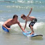 pai ensinando seu filho a surfar — Foto Stock