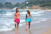 Two young beautiful tanned women walking along sandy beach — Stock Photo