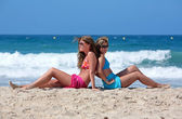 Two young attractive women chilling in the sun on holiday or vac — Stock Photo
