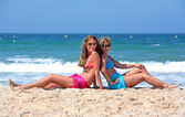 Two young sexy and healthy girls sitting on a sunny beach — Stock Photo