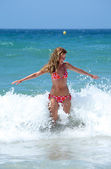 Sexy fit young woman being splashed by a wave — Stock Photo