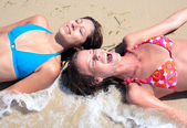 Two young attractive women splashed by cold wave on the beach — Stock Photo