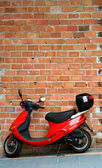 Red moped or motorbike resting or leaning against a brick wall — Stock Photo
