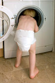 Young child climbing inside a washing machine — Stock Photo