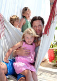 Young father and children sitting in a hammock on vacation — Stock Photo