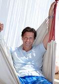 Bonito homem envelhecido médio sentado na cama de rede — Foto Stock