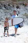 Man and his son arriving at the beach to surf — Stock Photo
