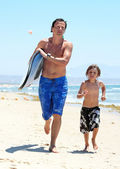 Young father and son running along beach with surfboard — Stock Photo