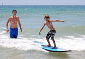 Happy father teaching his young son to surf — Stock Photo