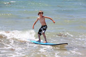 Healthy young boy learning to surf — Stock Photo