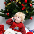 Stock Photo: Young boy or toddler talking on mobile phone under christmas t