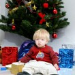 Young boy or toddler sitting under a christmas tree — Stock Photo