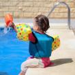 Girl toddler sitting next to swimming pool — Stock Photo
