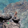 Aerial view of young woman fishing on rocks with net — Stock Photo