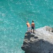 Aerial photo of two young boys on rock looking into sea — Stock Photo #6232065