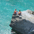 Aerial photo of two young boys on rock looking into sea — Stock Photo