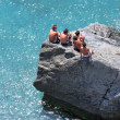 Stock Photo: Five young boys sitting rocks watching the day go by