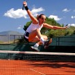 Girl jumping tennis net - Stock Photo