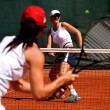 Two young sporty female tennis players having a game in the sun. - Stock Photo