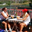 Two women enjoying a cold drink after a game of tennis in the su — Stock Photo #6232733